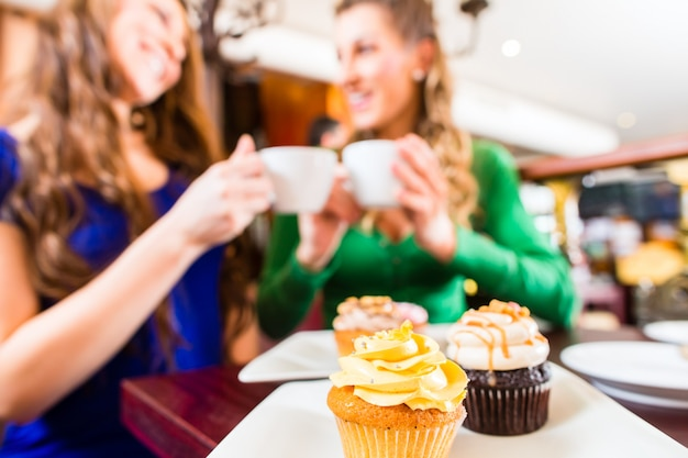 Women eating muffins while coffee drinking