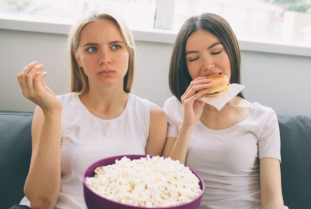 Women eating popcorn and burger, and watching tv