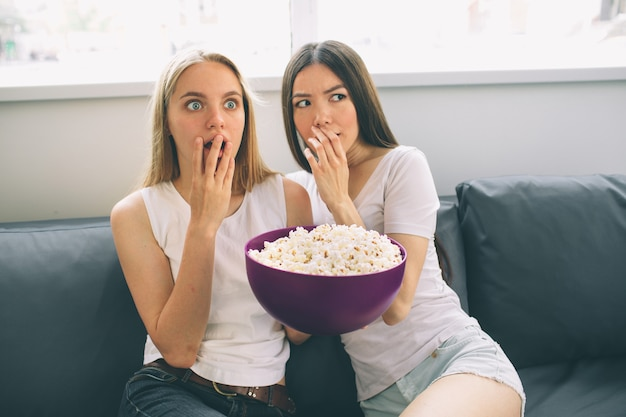 Women eating popcorn and watching tv