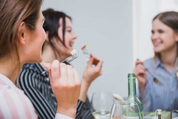 Women eating snacks with forks