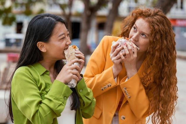 屋外で屋台の食べ物を食べる女性