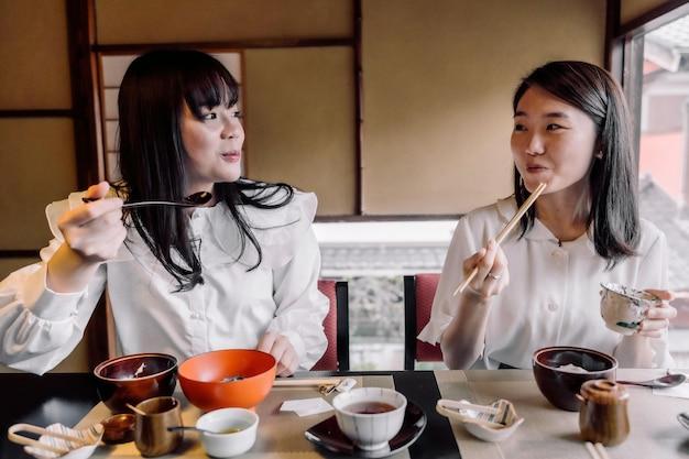 ミディアムショットを一緒に食べる女性