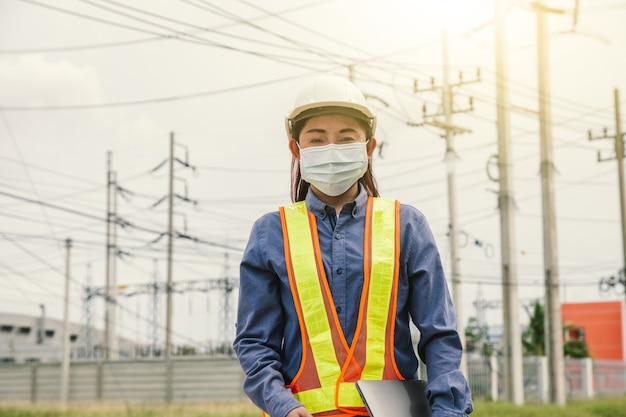 Женщины, инженер по электричеству, работающие на месте обслуживания с компьютером