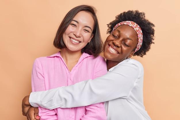 女性は抱き合って友好的な関係を持っていますカジュアルな服を着てお互いを愛し、ベージュで隔離された一緒に時間を過ごすことを楽しんでください