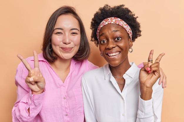 여자 포옹과 승리 제스처 미소를 긍정적으로 보여줍니다 평화 디스코 기호를 보여줍니다 함께 재미있게 옷을 입고 베이지 색에 고립 된 캐주얼