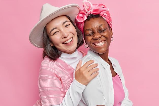 Женщины обнимаются и стоят близко друг к другу, широко улыбаются, носят стильную одежду, изолированную на розовом