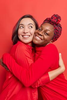 Le donne si abbracciano con amore hanno buoni rapporti indossano abiti rossi sorridono piacevolmente posano al chiuso