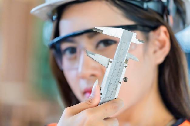工場でハード帽子を着用する工業エンジニアは、ノギスを使用して工場で働いています。