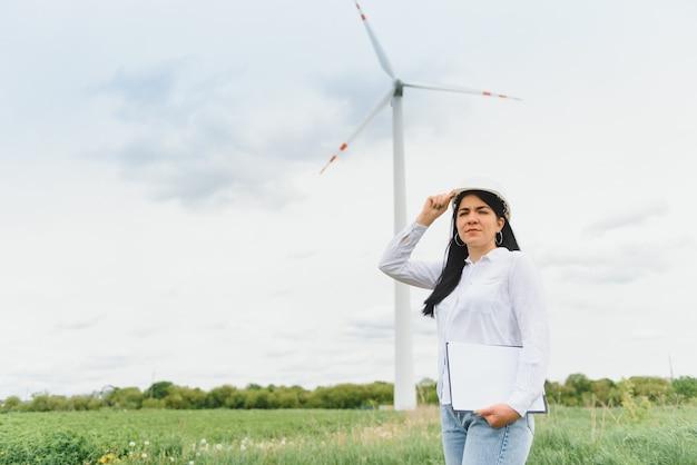 Женщины-инженеры работают и держат отчет на электростанции ветряных турбин на горе