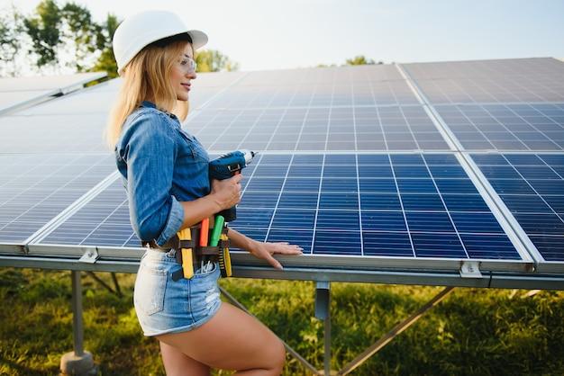グリーンエネルギー太陽光発電所で機器のチェックに取り組んでいる女性エンジニア:タブレットのチェックリストでソーラーパネルと構造をチェック