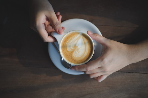 ホットカプチーノのコーヒーカップを飲みながら、女性はカフェでコーヒーを飲むのを楽しんでいます