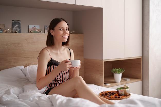 Donne che godono del caffè con marshmallow sul letto con presente vicino a lei. mattina sorpresa