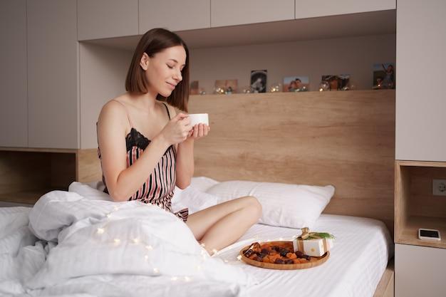 Donne che godono del caffè con marshmallow sul letto con presente vicino a lei.