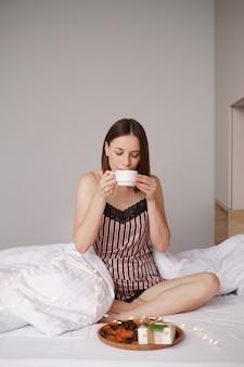 ベッドの上でマシュマロと一緒にコーヒーを楽しんでいる女性たち。