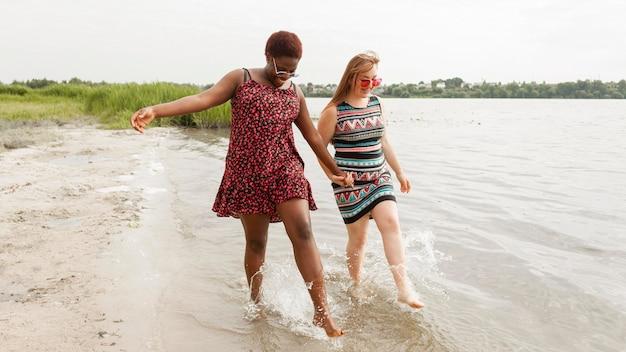 一緒にビーチで水を楽しむ女性
