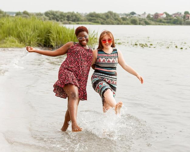ビーチで一緒に水を楽しむ女性