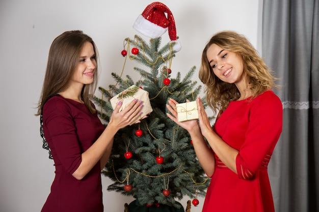 크리스마스 트리 근처에서 선물을 교환하는 여성
