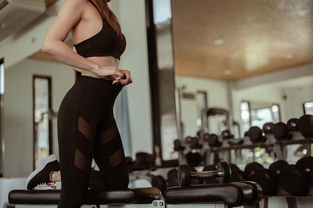 鏡で体のプロポーションをチェックする健康のために、女性は屋内ジムでダンベルで運動します