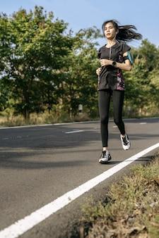 女性は道路を走って運動します。