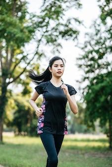 女性は公園の路上を走って運動します。