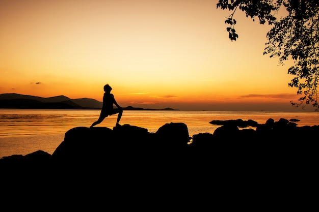Women exercise and relax on beach sunset background