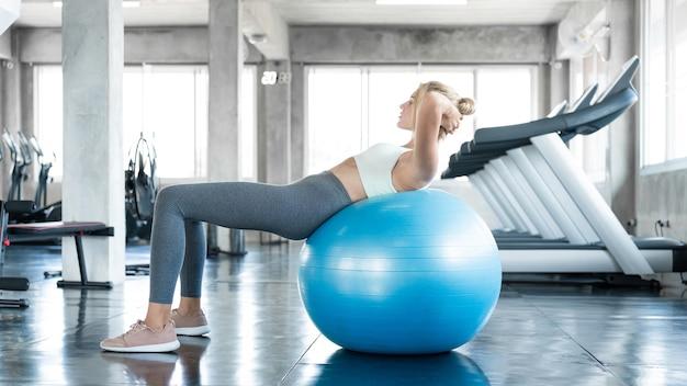 女性はジムの健康とフィットネスのコンセプトでボールを使って運動します