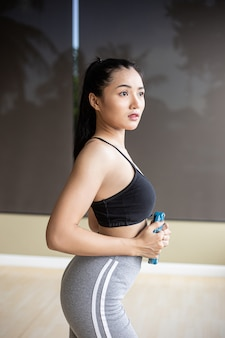 Women exercise with dumbbell weight plates on the abdomen.