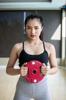Women exercise with dumbbell weight plates in the chest.