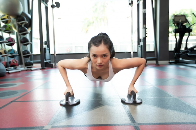 Women exercising by pushing the floor with fitness push up stands in gym