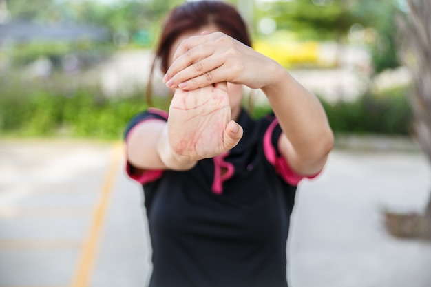 Women exercising. closeup of woman stretching his hand, wrist, and forearm.