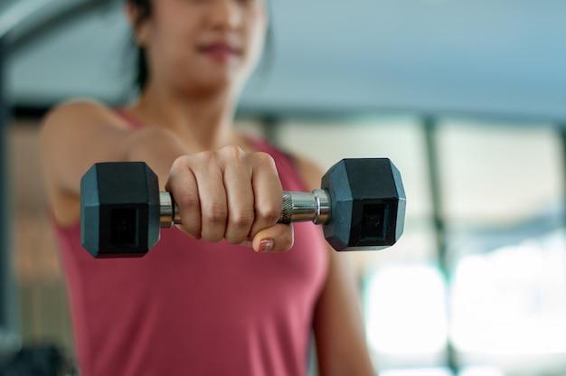 ジムで運動している女性。ダンベルを前に出して強い姿勢で持ち上げる手の重量挙げ姿勢。健康を維持するための運動の概念。自宅で運動する