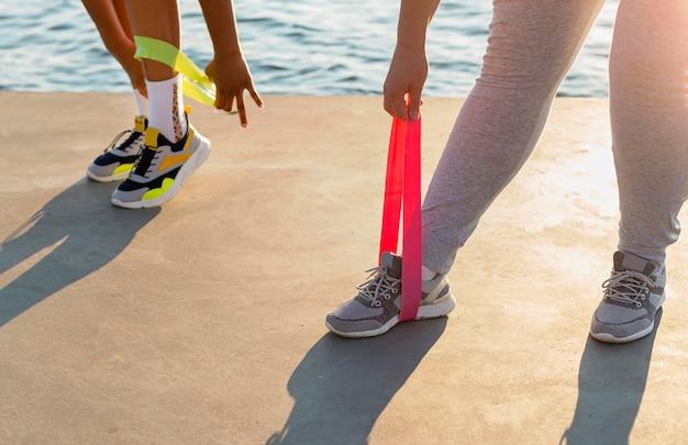 Женщины тренируются с резинками на берегу озера