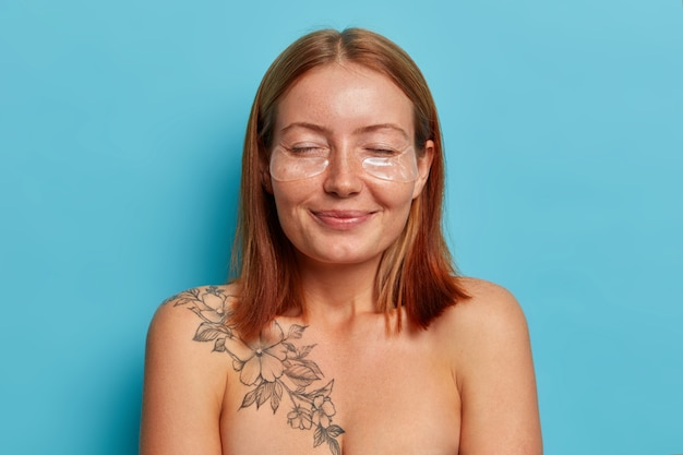 女性、フェイスケア、美容のコンセプト。陽気な笑顔の赤毛の女性は目を閉じて立って、ヒドロゲルパッチを適用し、滑らかなきれいな肌、手入れの行き届いた体を持ち、青い壁に対して裸でポーズをとる