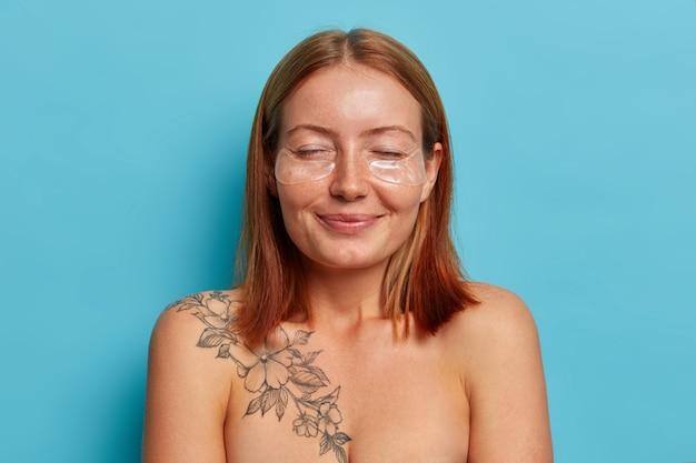 Donne, cura del viso e concetto di bellezza. allegra donna rossa sorridente sta con gli occhi chiusi, applica cerotti di idrogel, ha una pelle liscia e pulita, un corpo ben curato, posa nuda contro il muro blu