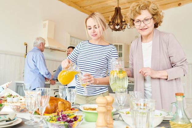Women of family setting dinner table