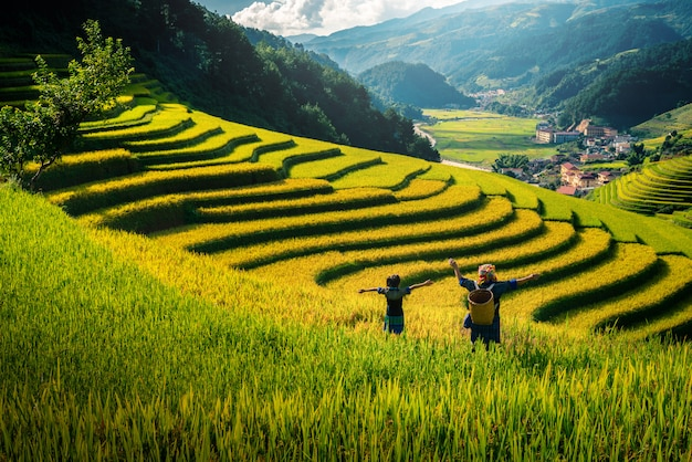 Women farmer and daughter raising arm on rice fields terraced at sunset in vietnam.
