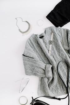 女性のファッションの布やアクセサリー。暖かいセーター、ジーンズ、財布、時計、サングラスを備えたフラットレイの女性のカジュアルなスタイルの外観