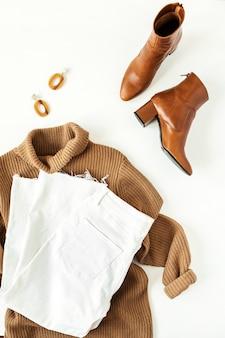 여성 패션 의류, 흰색 액세서리. 평면 위치, 최고보기 최소한의 유행 라이프 스타일 콜라주. 브라운 터틀넥 스웨터, 신발, 청바지, 귀걸이
