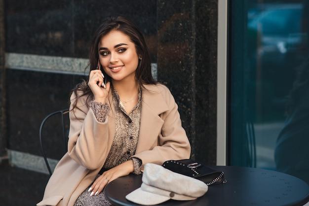 女性のファッション。完璧なメイクと髪型の女性。外の喫茶店で魅惑的な女の子。テクノロジーとライフスタイル。屋外のカフェに座っている携帯電話を持つファッショナブルな女の子。都市のライフスタイル。