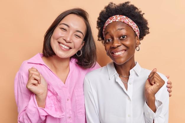 여성들은 매우 행복한 포옹을 느끼고 셔츠를 입은 주먹을 쥔 채 베이지색으로 격리된 서로 가까이 서 있다