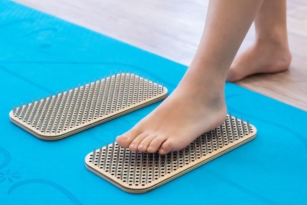 女性の足は鋭い爪のあるボード、サドゥーボードの上に立っています。ヨガの練習。痛み、試練、健康。青いヨガマット。