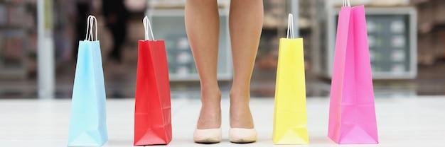 쇼핑몰에서 여러 가지 빛깔의 종이 쇼핑백 옆에 서 있는 신발을 신은 여성의 발