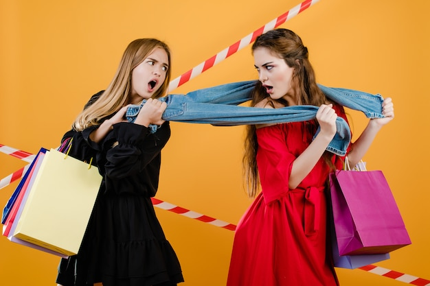 Women fighting over pair of jeans with colorful shopping bags and signal tape isolated over yellow