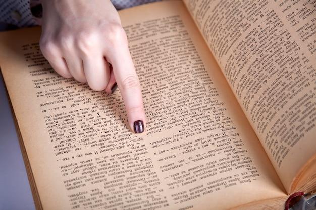 Палец женщин указывая на страницу книги. закрыть просмотр.