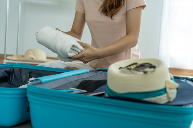 Женщины складывают одежду в пакеты, чтобы подготовиться к предстоящему отпуску. Premium Фотографии
