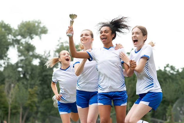 カップを保持している女性のサッカーチーム