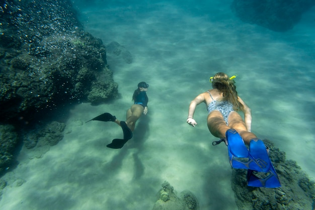 Women freediving with flippers underwater