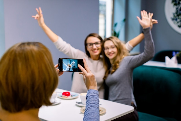Women friends in cafe indoors. two pretty women friends hugging, with hands up and posing for the photo together, while her third friend woman is taking a picture on the smartphone