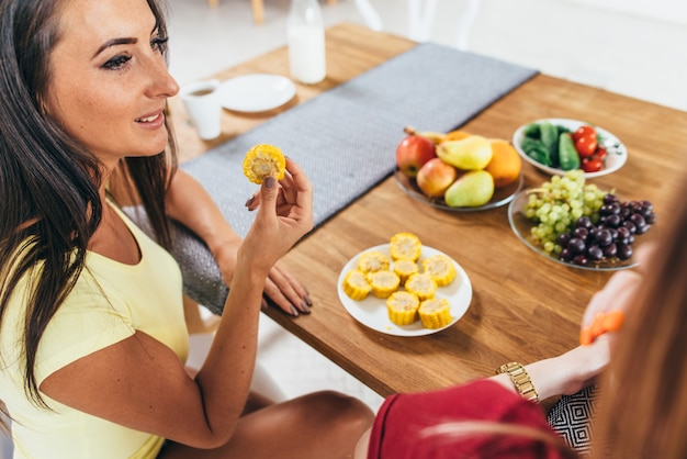Women friends eating fruits and vegetables in kitchen. healthy nutrition. low calorie meal.