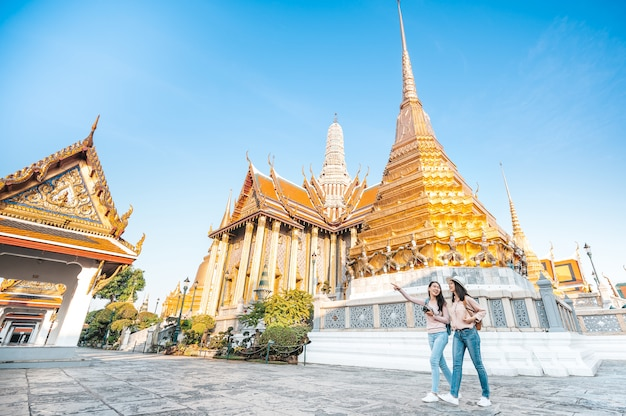 Women friends enjoy sightseeing while travel in temple of the emerald buddha in thailand